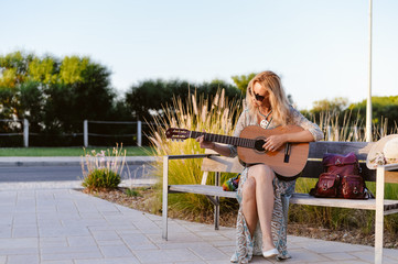 Portrait of a beautiful blond female playing guitar on an old wooden bench, sunny blue sky outdoors background