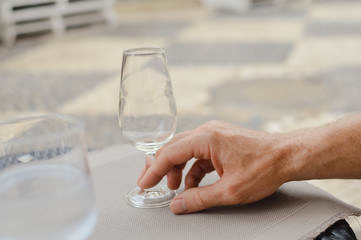 Closeup view of male hand holding a wine glass, table background