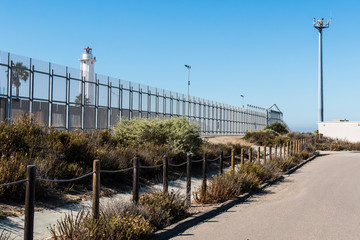 Tijuana lighthouse on the Mexico side and a security tower with cameras and motion sensors on the US side.