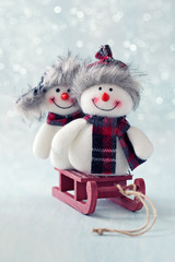 Two funny Snowmen on a sled. Christmas background. Christmas card.