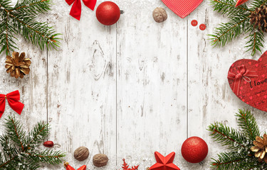 White wooden table with christmas tree and decorations top view. Free space for text. Christmas balls, bow, walnut, pincone, stars and gift beside.
