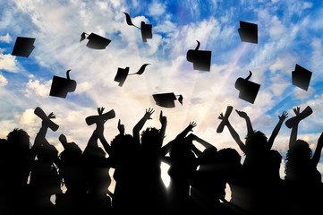 Students graduate cap throwing in sky