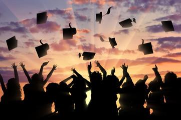Graduates sunset throw graduate cap