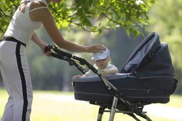 mother walking with a baby and a stroller in the park