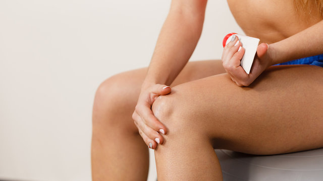 Woman fit girl putting ointment on injury knee