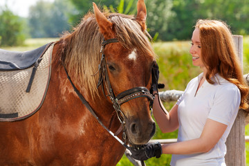 Happy young woman feeding her beautiful bay horse