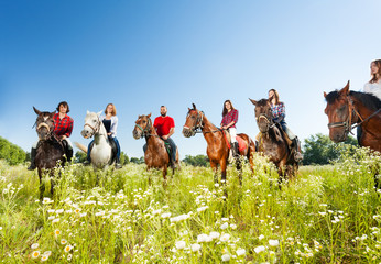 Poster de jardin Equitation Big group of horseback riders in flowery meadow