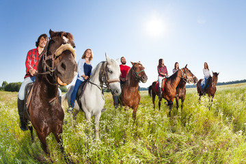 Poster de jardin Equitation Happy equestrians riding horses in summer meadow