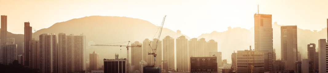 Hong Kong aerial cityscape panorama view with building construction near Victoria Harbor at sunset....