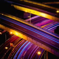 Abstract night view of highway interchange with moving cars. Hong Kong city aerial background