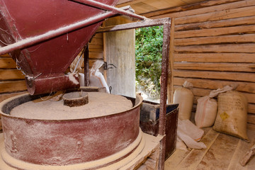 Inside an old functional water mill Grinding