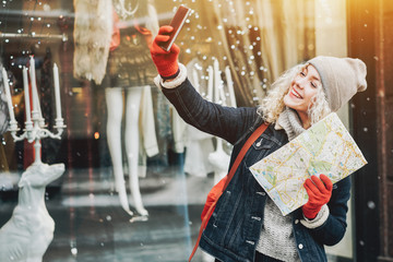 Smiling curly blond girl with map making selfie, winter