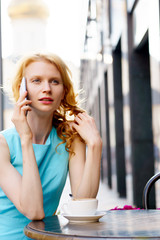 Portrait of curly blonde woman talking on cellphone in cafe