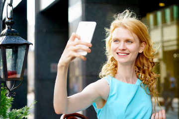 Cheerful young woman photographing herself on phone
