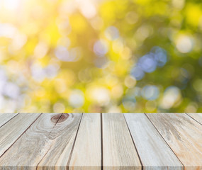 Wood table top on shiny sunlight bokeh background for display montage