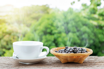 Hot coffee cup and coffee beans in the bamboo plate on the old wooden floor with colorful green nature background.