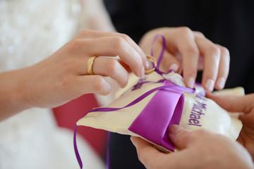 Ringkissen mit Eheringen - Braut entnimmt den Ring