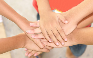 To join hands to show unity and team spirit.