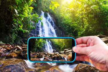 Making photos by smartphone of amazing waterfall