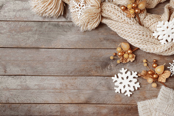 Knitted scarf and Christmas decor on wooden background