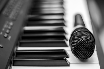 Close up microphone on piano keyboard in music studio. Music concept.
