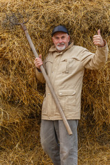 An elderly man is standing at the haystacks