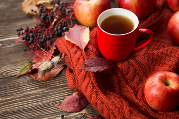 Hot drink and autumn leaves on vintage wood background - seasonal relax concept
