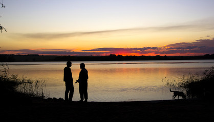 men and dog silhouette at sunset lake