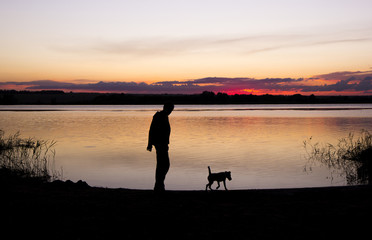 boy and dog silhouette at sunset lake