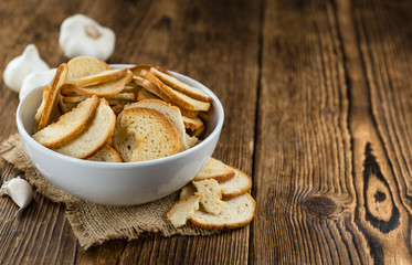 Bread chips on wooden background