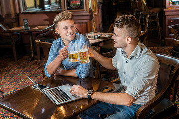 Beer and laptop. Two businessmen friends men drinking beer and h