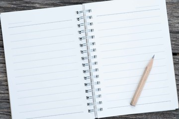 Open blank notebook and pencil on wood background.