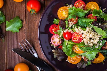 Fresh healthy salad with quinoa, cherry tomatoes and mixed greens (arugula, mesclun, mache) on wood background top view. Food and health. Superfood meal. Wall mural