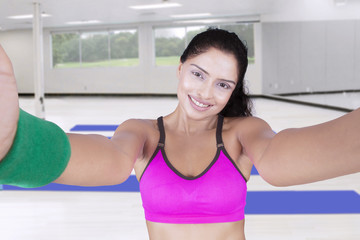 Attractive Indian woman taking selfie at gym