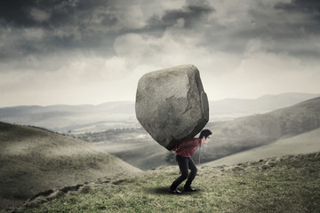 Businessman carrying rock at hill