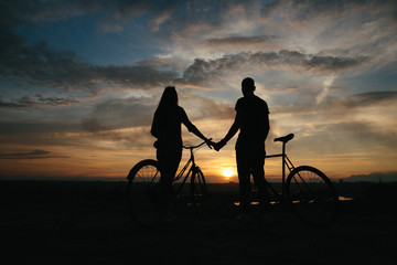 Silhouette couple with bicycles looking at a beautiful sunset
