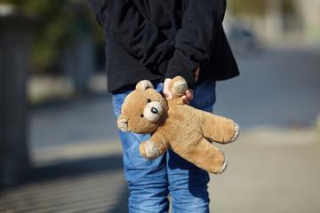 little homeless boy holding a teddy bear