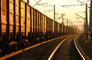 Freight train moving on the tracks at sunset