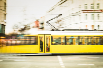 Blurred motion of defocused yellow tram on the streets of Berlin - Transport concept with public vehicle speeding at rush hour on city road - Warm vintage filter with blurry composition