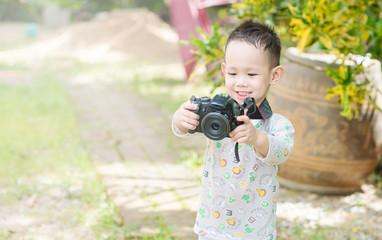 Asian kid take a photo by DSLR camera
