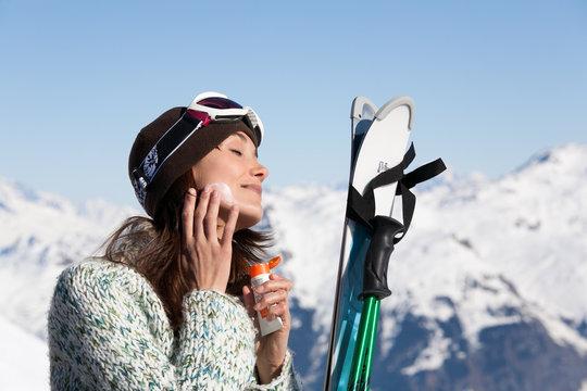 portrait d'une belle femme se mettant de la crème de protection solaire en hiver à la montagne
