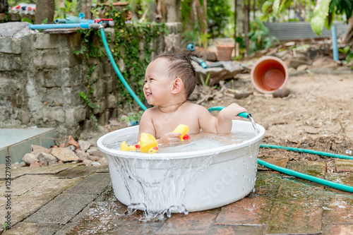 top view asian baby boy outdoor bathing in the white bathtub h stock photo and royalty free. Black Bedroom Furniture Sets. Home Design Ideas