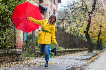 Enjoying autumn days. Woman in yellow raincoat walking down the street