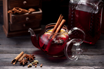 Mulled wine with spices on wooden background