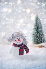 Greeting card with a snowmen on a snowy background .