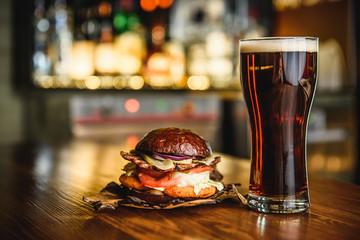 Hamburger and dark beer on a pub background.