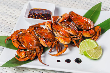Cooked crab with sauce and lime on a plate