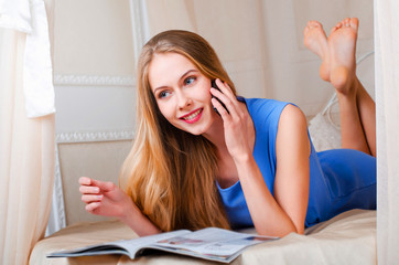 beautiful young blond girl in blue overalls lies on a bed in a cozy room and talking with someone on the phone and smiling