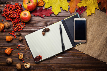 notebook, pen and telephone in autumn still life, fall leaves, gifts of autumn,  wooden background, walnuts, maple leaves - autumn composition from top. Free space for text. Colorful autumn leaves