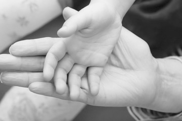 Mother's and baby's hands, black and white